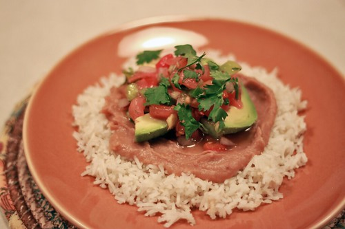 Red-orange plate with a bed of white rice topped with refried beans, pico de gallo, avocado slices, and cilantro.