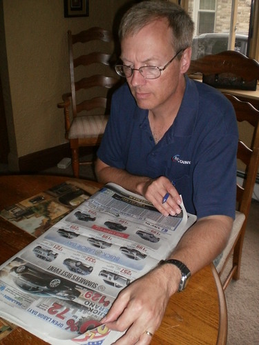 Mike looking through car ads in the paper