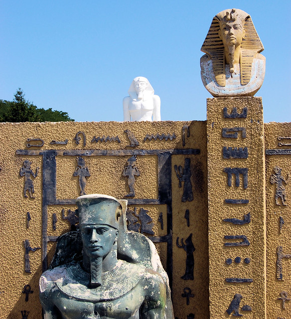 Picture shows the statue of a war Pharaoh on the ground, bust of Tut on wall column, and colossus of Ramses in background