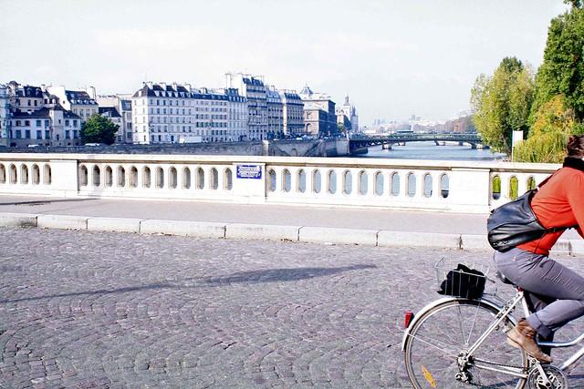red cyclist on seine bridge paris