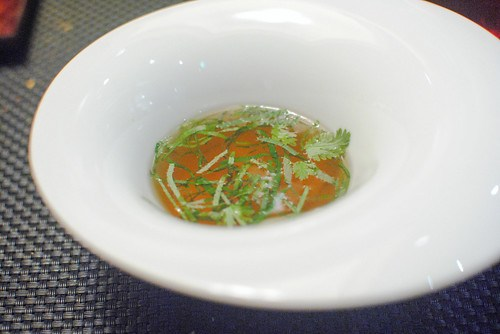 Les Ravioles foie gras ravioli in a warm chicken broth with herbs and spicy cream