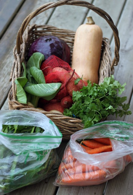 Basket filled with squash cabbage, sweet potatoes, and more. In front are two bags, one of spinach and one of carrots.