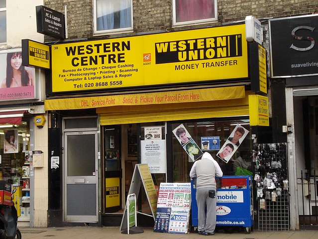 a terraced shopfront with a yellow sign reading western centre western union money