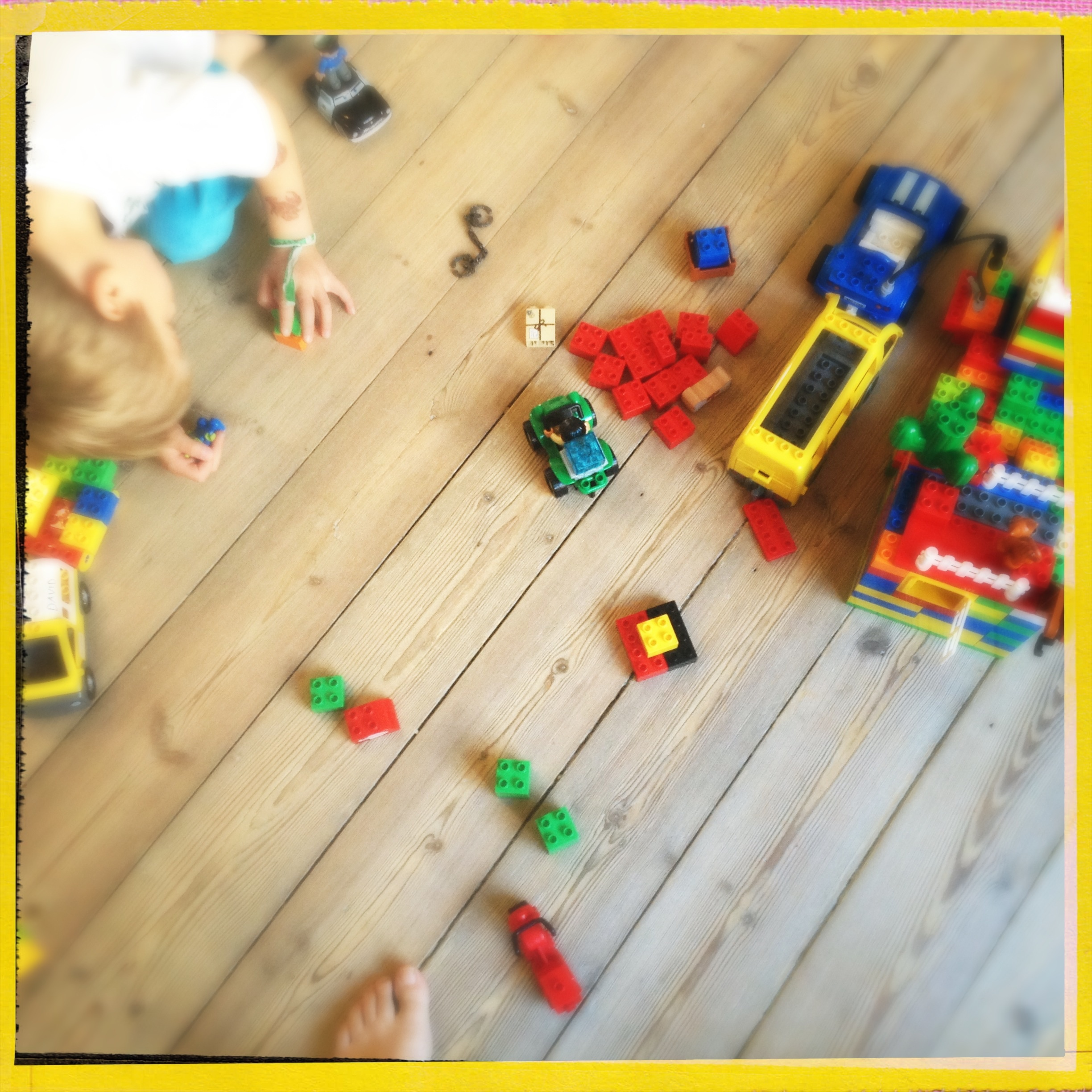 Boy playing with lego on natural wooden floor
