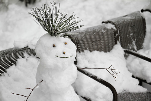 Park benches covered in snow and surrounded by deep drifts; a small snowman with a cheerful face and twigs making spiky hair is sitting on a seating space