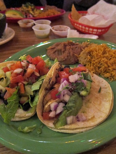 Green plate with two fully loaded tacos, a pile of rice, and a scoop of refried beans.