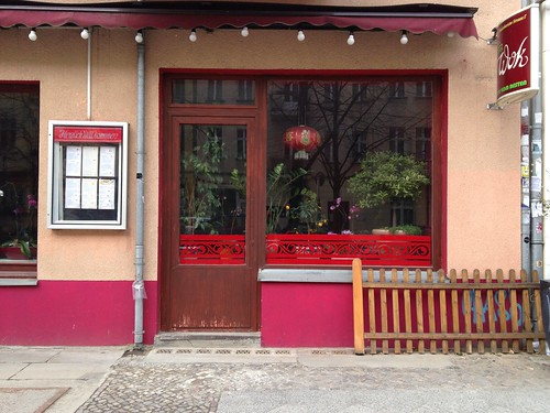 Facade of closed restaurant with window full of plants