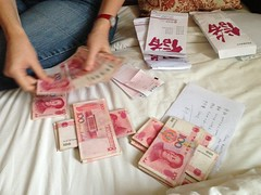 Sophie counting out Chinese money in to piles of 100 Yuan bills
