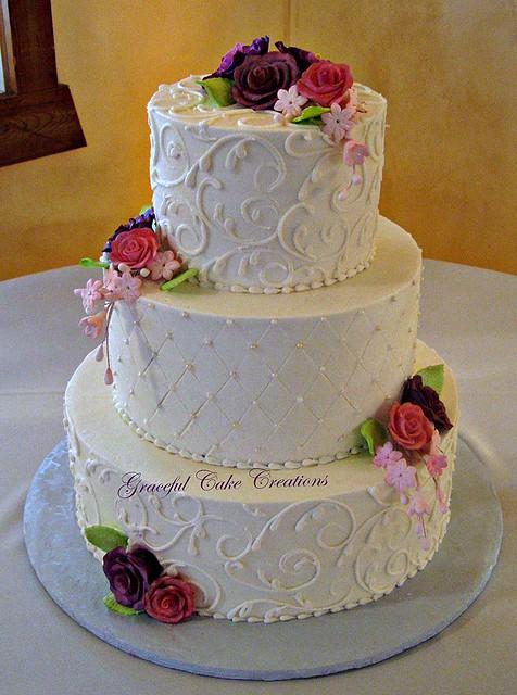 Elegant Ivory Buttercream Wedding Cake with Purple and Pi