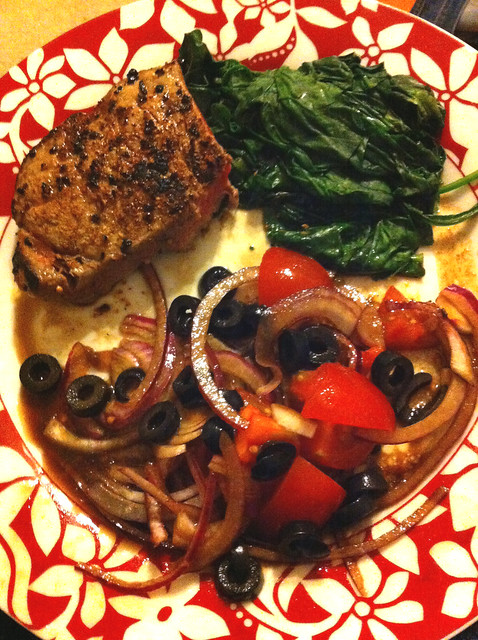 Peppercorn steak on wilted spinach with tomato salad