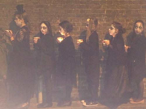 Candlelit procession on brick wall