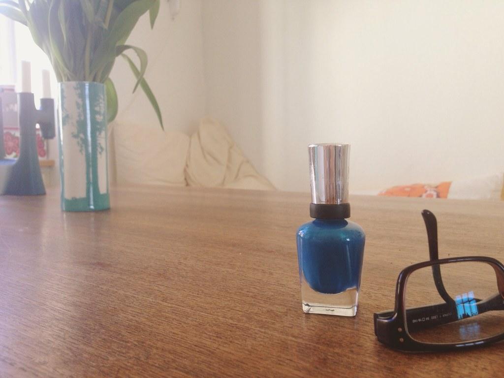 Glasses and blue nail polish