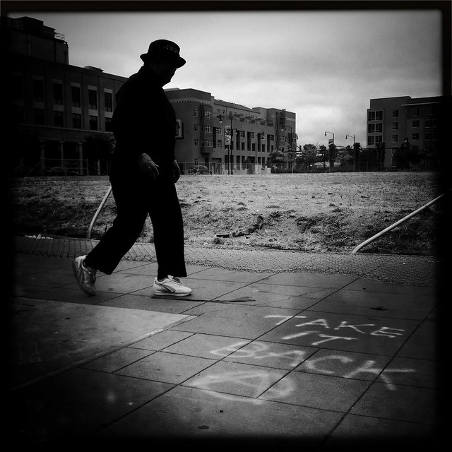 "Black and white photo of someone in Oakland walking near graffiti that says ""Take it back! Circle-A!"""