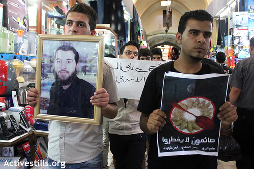 Palestinian activist holds Hassan Safadi's picture during a demonstration in the old city of the West Bank city of Nablus in solidarity with the Palestinian prisoners who are still on hunger strike; Samer Barq, Hassan Safadi, Ayman Sharawna and Raed Jamal, August 09,2012.
