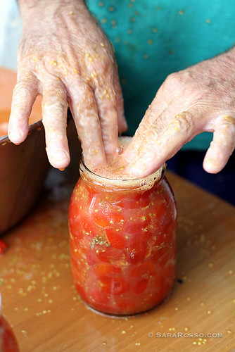 Stuffing tomatoes into a jar in Italy