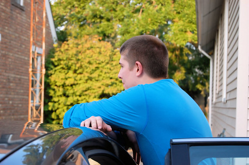 Aaron leaning on the roof of his car smiling and talking with his father