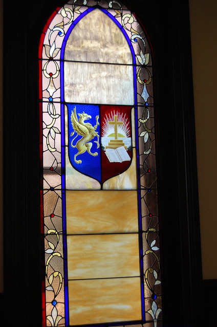 Window is done in red, white, and blue glass with a gold griffin and a gold cross.