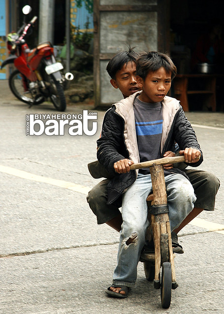 Ifugao kids riding wooden carved scooter