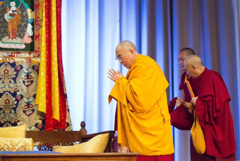 The dalai lama in a yellow robe with two acolytes in red bow to the left