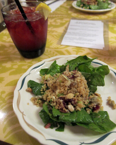 Bed of baby spinach leaves with a quinoa salad studded with dried cranberries.