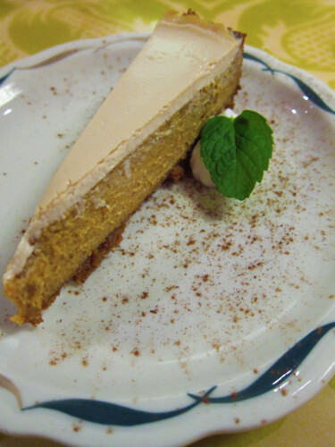 Small sliver of a light orange cheesecake on a white plate, sprinkled with cinnamon.