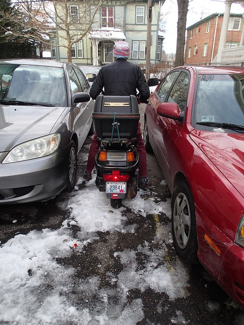 Squeezing the Honda Elite 250 between the tenants' cars