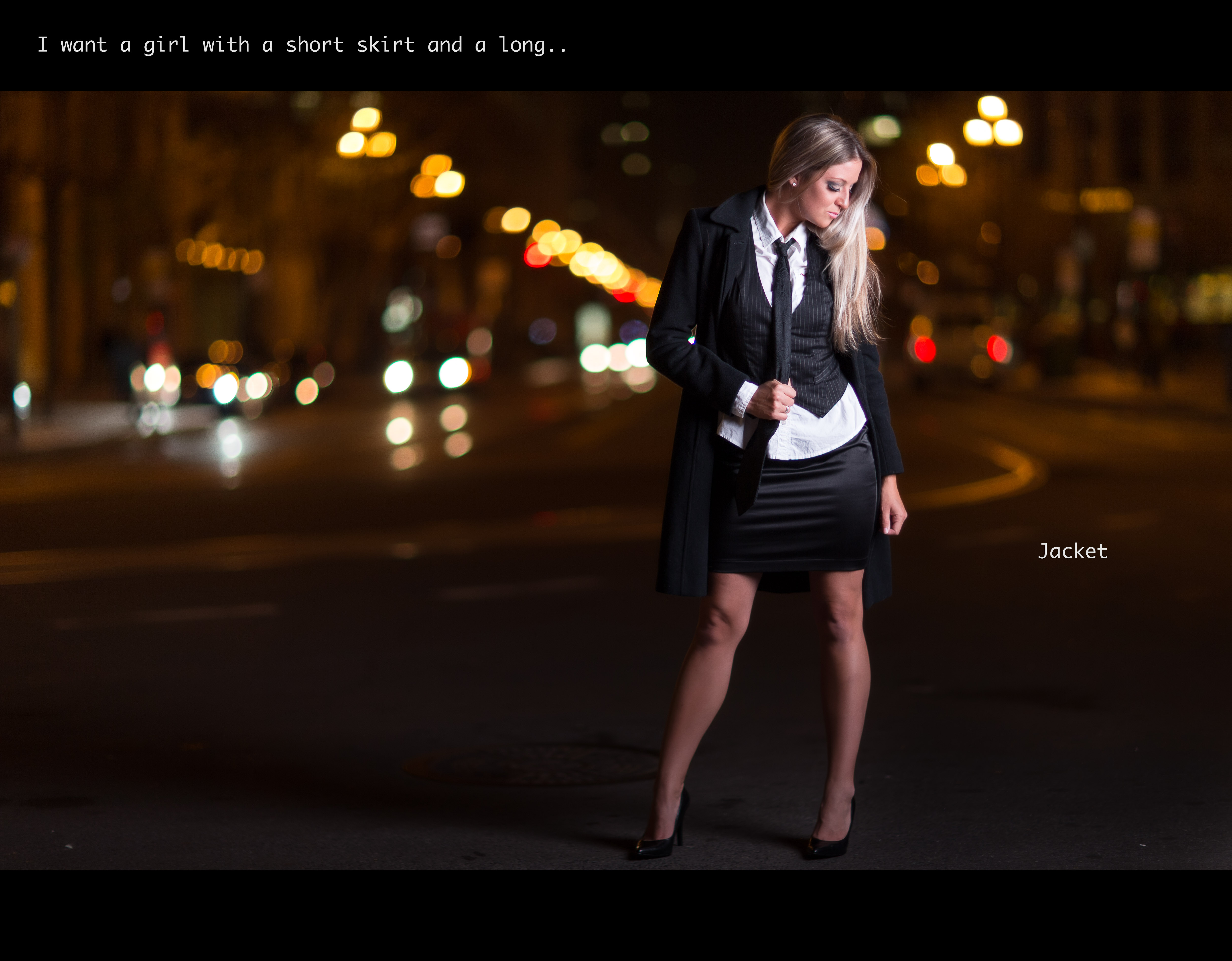 Picture of a woman standing on a street at night. She is wearing a vest and tie, a short skirt, and a long... jacket.