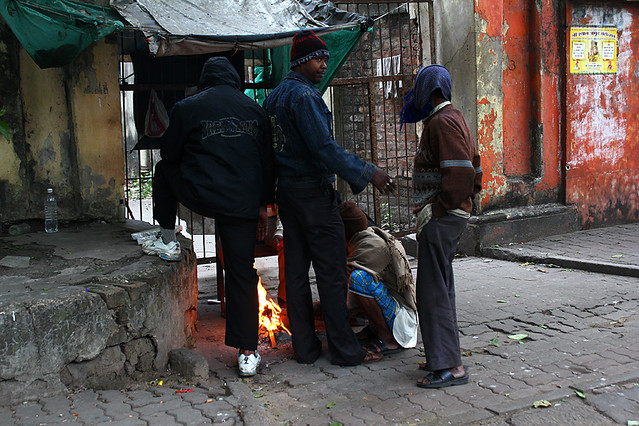 Men gathering around a small fire on the street