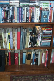 The other half of the bookshelf with books and DVDs vying for space in it.