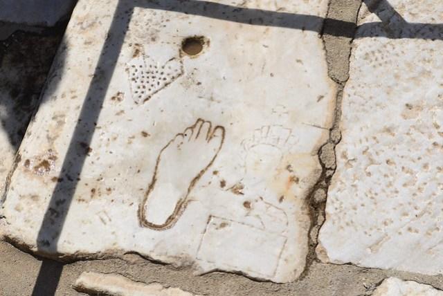 艾菲索斯 (Ephesus) (古名 Efes) 是地中海地區保存最好的古羅馬遺跡,也是來到伊茲密爾 (Izmir) 的重點行程之一。位在 Izmir 南方約八十公里處,開車前往約一小時車程。門票 25 TL。依坡而建,南側入口地勢較高,一般旅行團皆由上而下較為省力,但實際走起來也不怎麼費力。古城也是有色情行業,此石板上刻著妓院的廣告:受傷的心(被戳很多洞),帶著鈔票(人像下方圖案)前往妓院(腳印,大小還可以用來評估是否已成年),就會有美麗的女子(人像)安慰你。