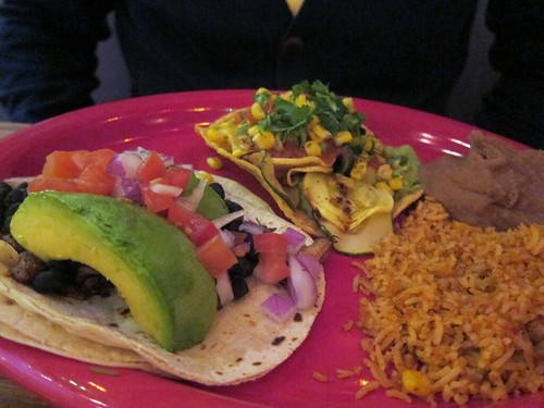 Magenta plate with an avocado-filled taco and a tostada piled high with veggies.