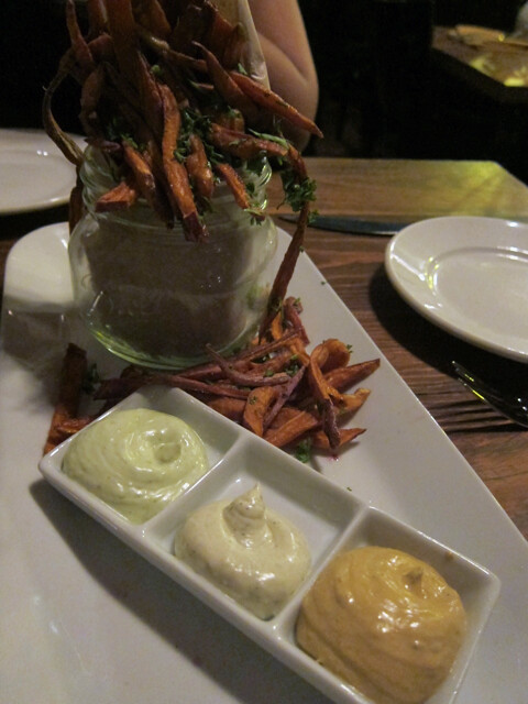 A big mason jar of shoestring sweet potato fries and three dipping sauces.