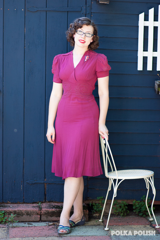 A casual outfit featuring a bold raspberry pink 1940s dress and modern blue sandals
