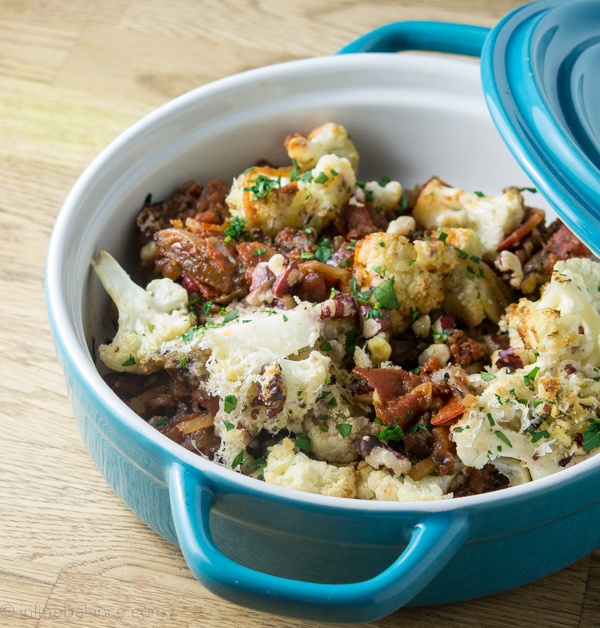 Cauliflower Gratin with Tomatoes and pinenuts in a blue casserole dish with lid