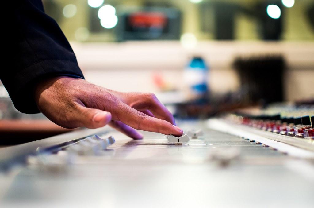 Imagen gratis de una mesa de mezclas y mano ajustando los controles