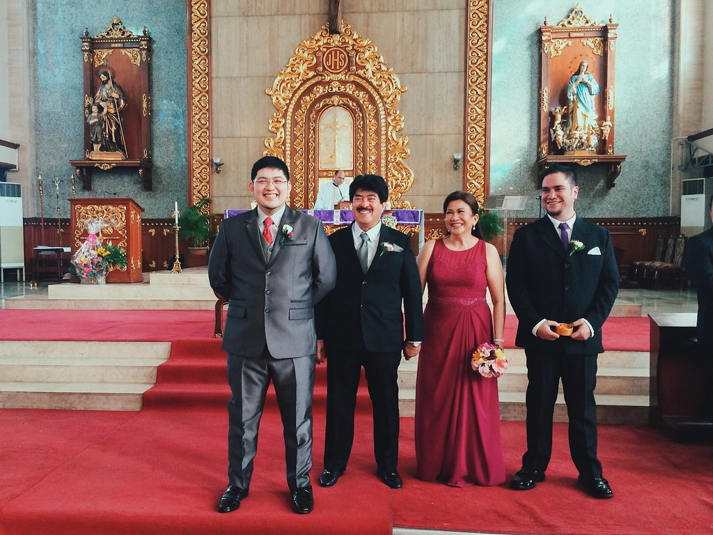 The groom, with his parents and the best man, waiting at the altar
