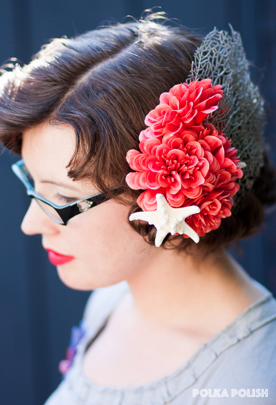 A handmade flower hairpiece featuring bright coral pink flowers, silver faux coral fronds, and dried starfish