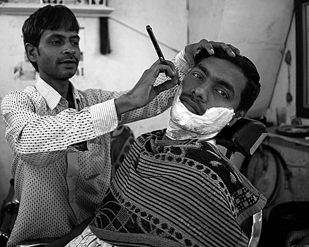 Imagen gratis de un barbero afeitando a un cliente