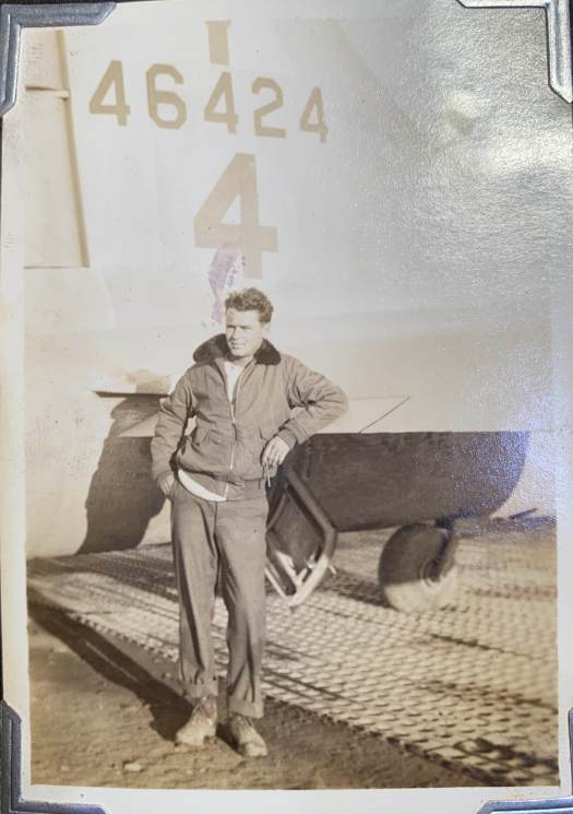 RW Moore standing at the tail of his B-17 in Italy during World War II