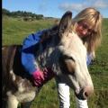 Lady cuddling donkey in a field