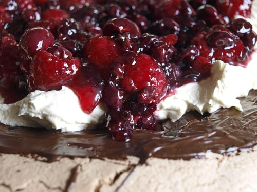A close up of chocolate meringue, berries and cream in Chocolate Berry Pavlova