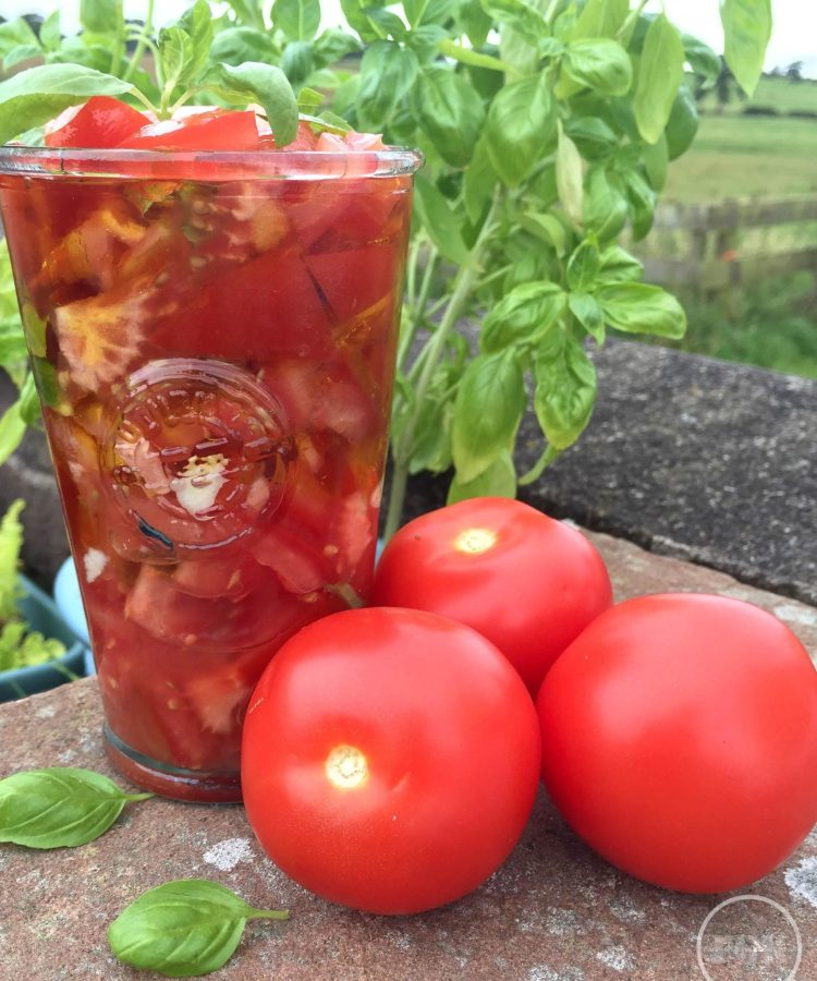 A simple tomato salad in a jar with basil and galrlic