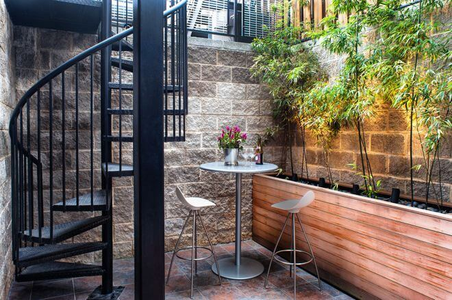 In an urban setting, any outdoor space is a luxury, even one below street level. You just have to make the most of it. A high-top table and tall planting bed complement the scale of this space. Leaves add softness and create a garden feel.