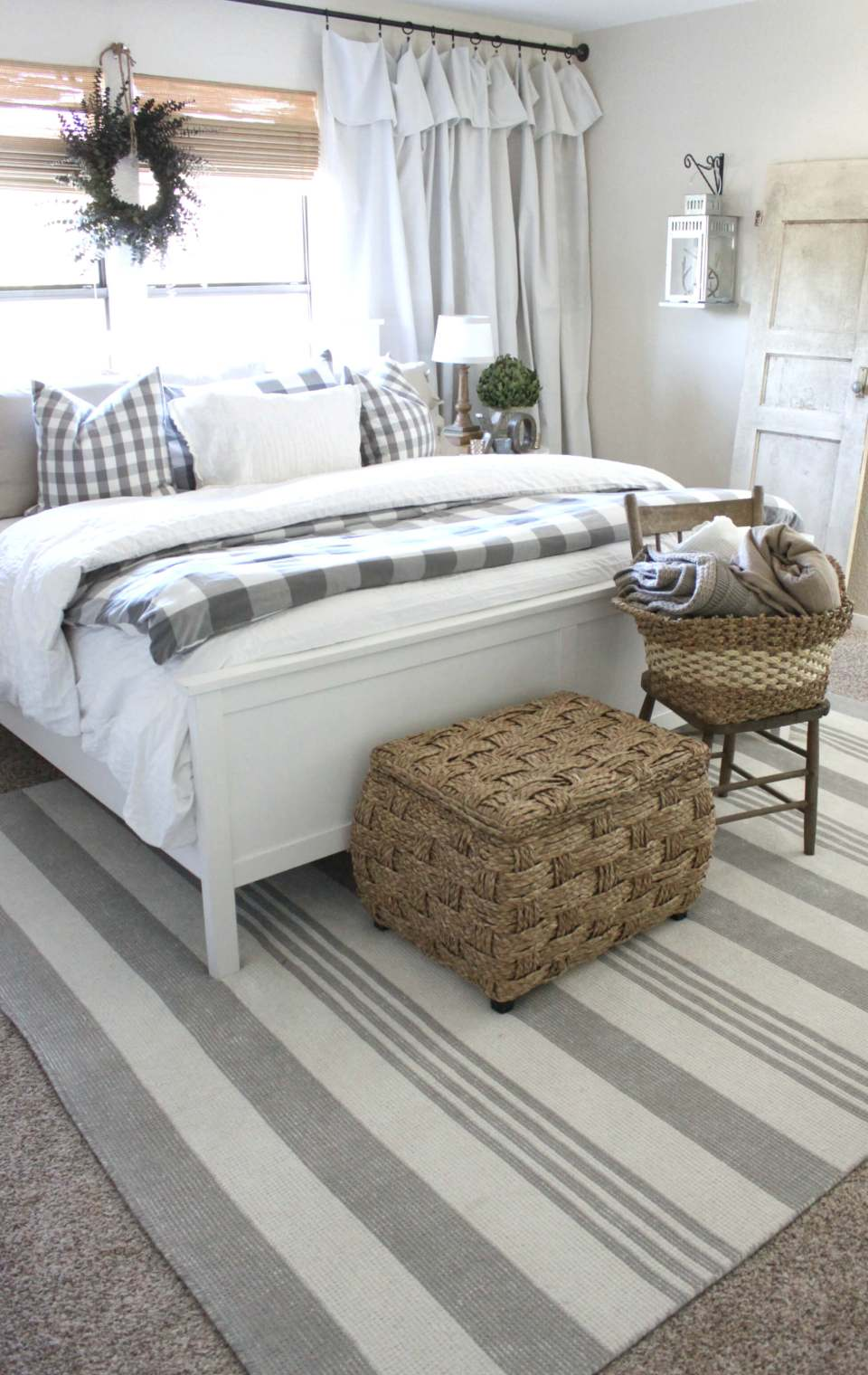 A white bed linens with a basket woven chest