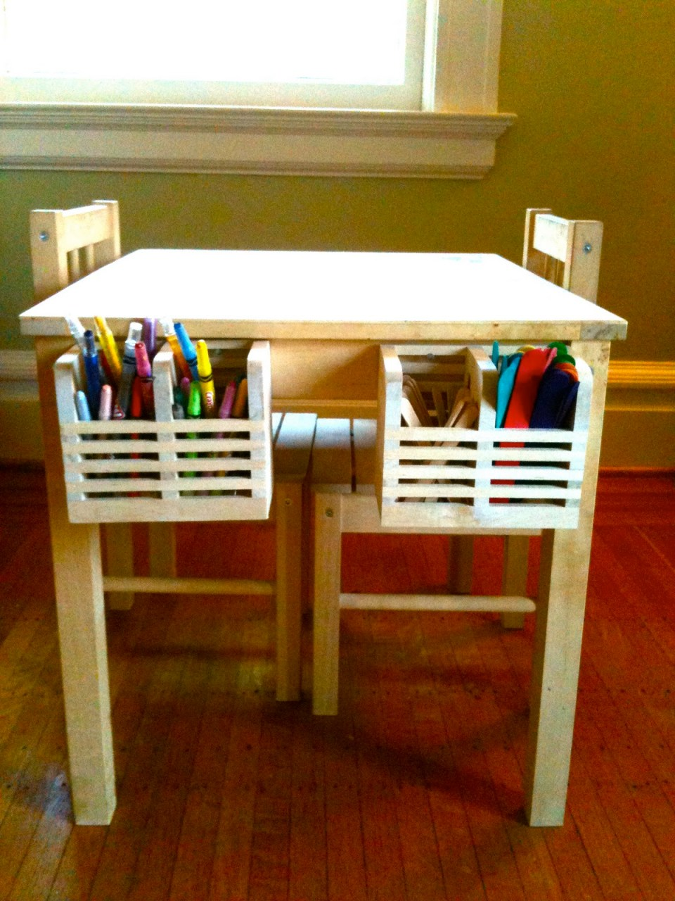 Children's table with two boxes placed inside that contain pencils