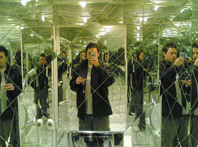 man taking a picture in a bathroom that is made of mirrors