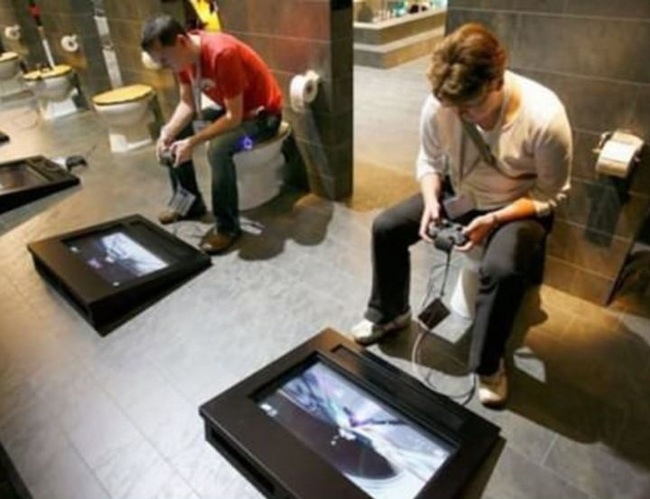 men sitting in the toilet and on the floor a screen with controls to play video games