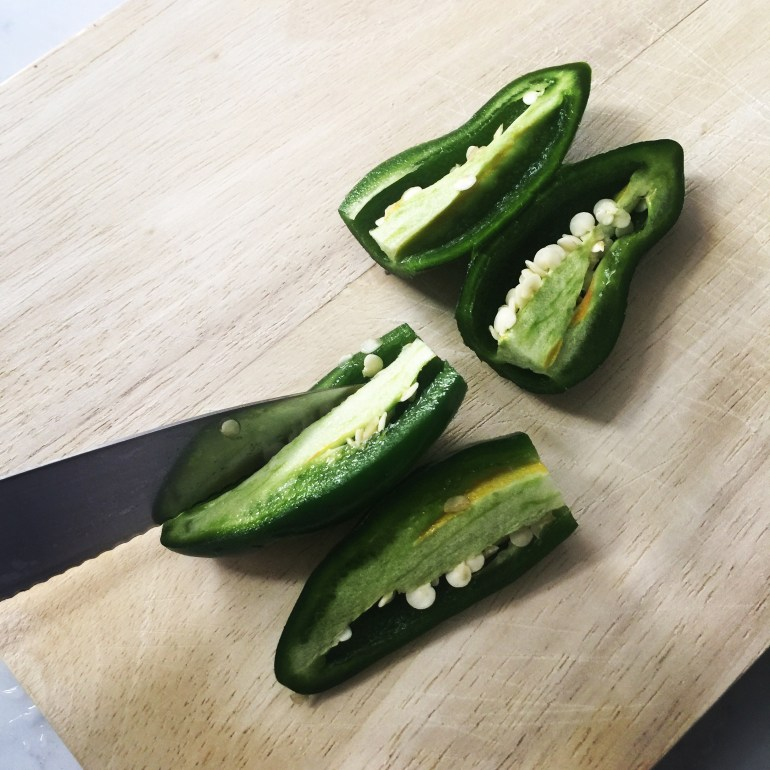 slicing jalapenos to remove the seeds on a cutting board
