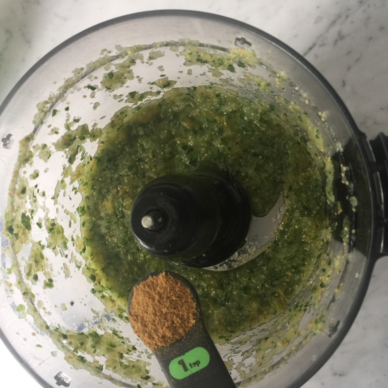 Fresh salsa in a food processor with cumin salsa verde jalapenos ground cherries