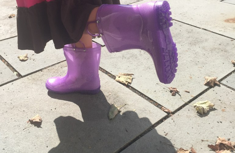 Kid wearing purple rain boots